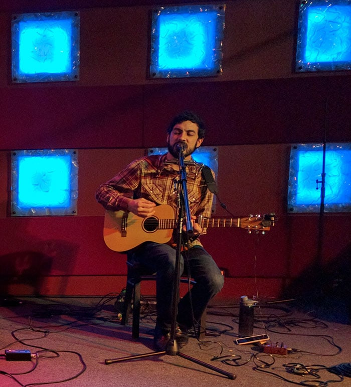 Zach Fountain performing on acoustic guitar at Iron Cactus Austin, 2015