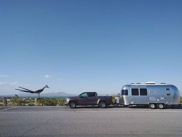 Roadrunner sculpture next to truck towing an Airstream travel trailer