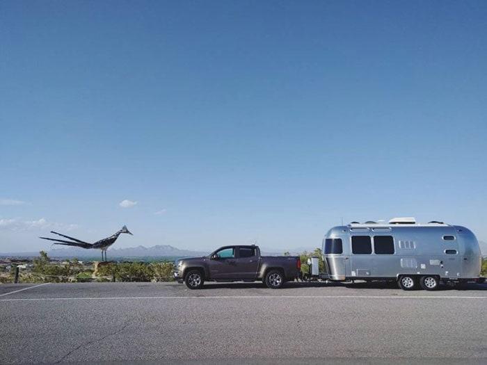 Roadrunner sculpture next to truck towing an Airstream travel trailer