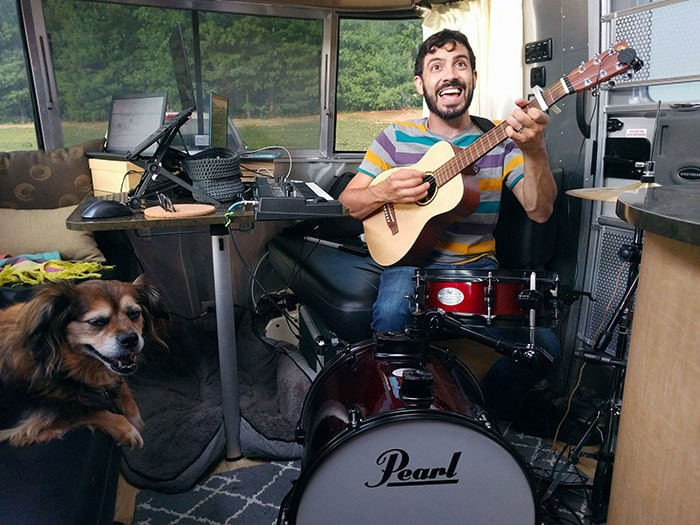 Zach sings, plays guitar and drums at the dining room table in his travel trailer.